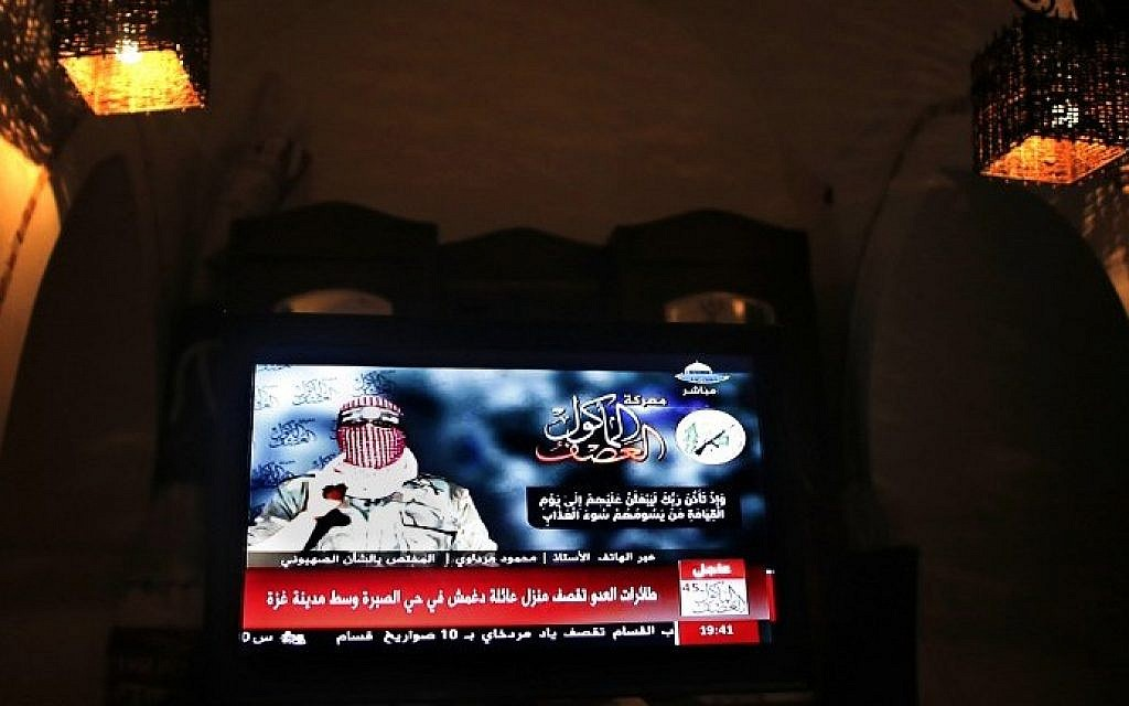 A television monitor displays the statement by Hamas spokesman Abu Obaida on Al Aqsa TV channel in Gaza City on August 20, 2014. photo credit: AFP/ THOMAS COEX)