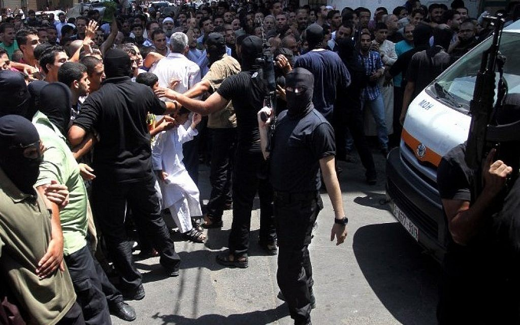 Armed Palestinian masked men push back a crowd of worshippers outside a mosque in Gaza City after Friday prayers on August 22, 2014, before executing 18 men for allegedly collaborating with Israel. (AFP)