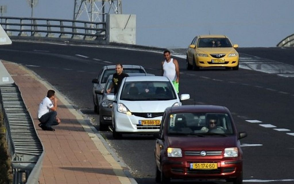 Israelis take cover as a siren wails in the southern costal city of Ashdod on August 22, 2014 (Photo credit: David Buimovitch/AFP)