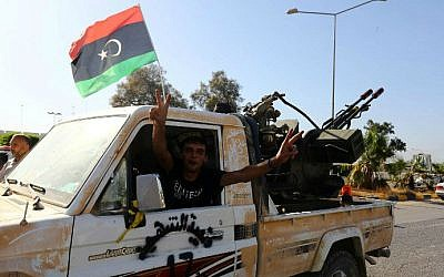 An Islamist fighter from the Fajr Libya (Libyan Dawn) coalition flashes the V sign for victory at the entrance of Tripoli international airport on August 24, 2014 (photo credit: AFP/MAHMUD TURKIA)