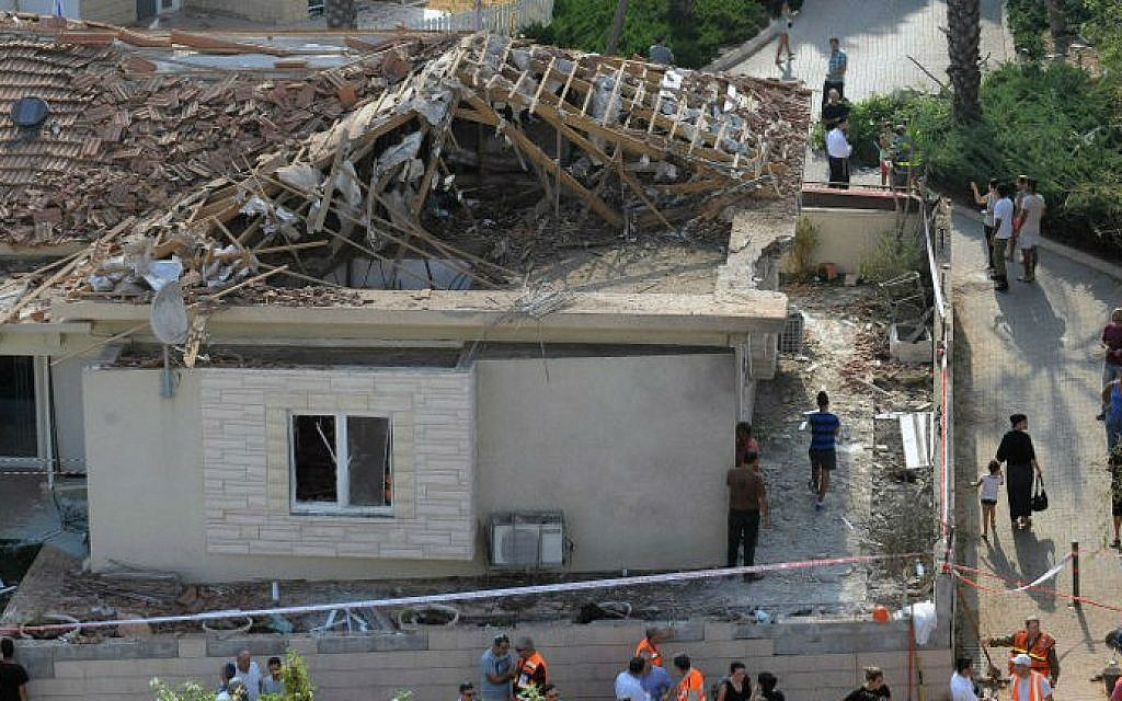 Residents and emergency services gather at the site of a damaged house in the Israeli coastal city of Ashkelon after it was hit by a rocket launched by Hamas terrorists in the Gaza Strip on August 26, 2014. (photo credit:AFP PHOTO/DAVID BUIMOVITCH)