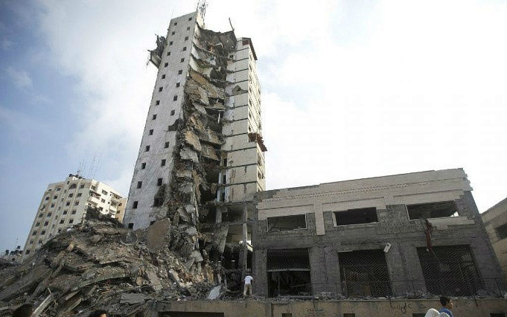 Palestinians look up at the remains of an apartment tower block that Israel said was used by Hamas as a command center and that was destroyed by an Israeli airstrike overnight in Gaza City on August 26, 2014. (photo credit: AFP/MAHMUD HAMS)