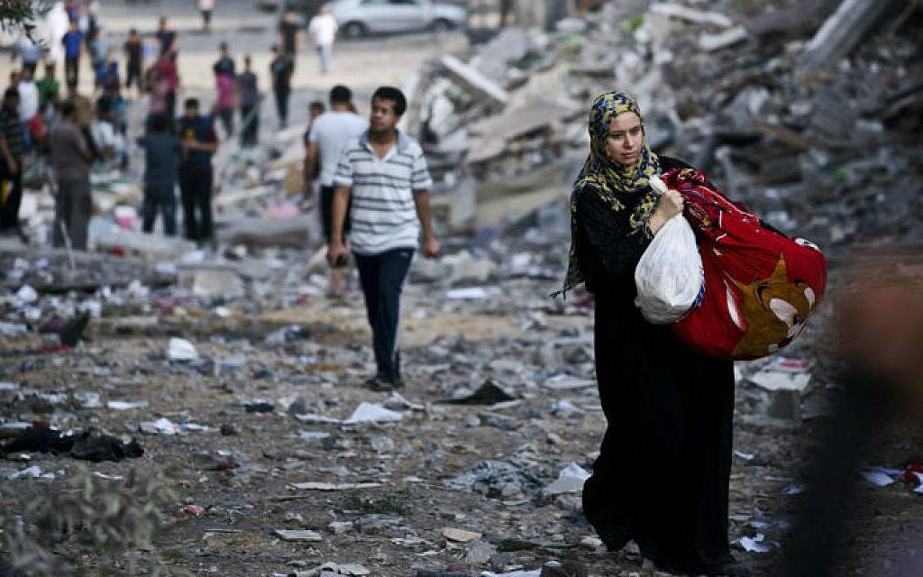 A Palestinian woman takes some of her belongings from her partially destroyed home across the street from where a high rise apartment building, that Israel said was used as a Hamas command center in Gaza City, was targeted by Israeli air strikes overnight on August 26, 2014.  (photo credit: AFP/ROBERTO SCHMIDT)