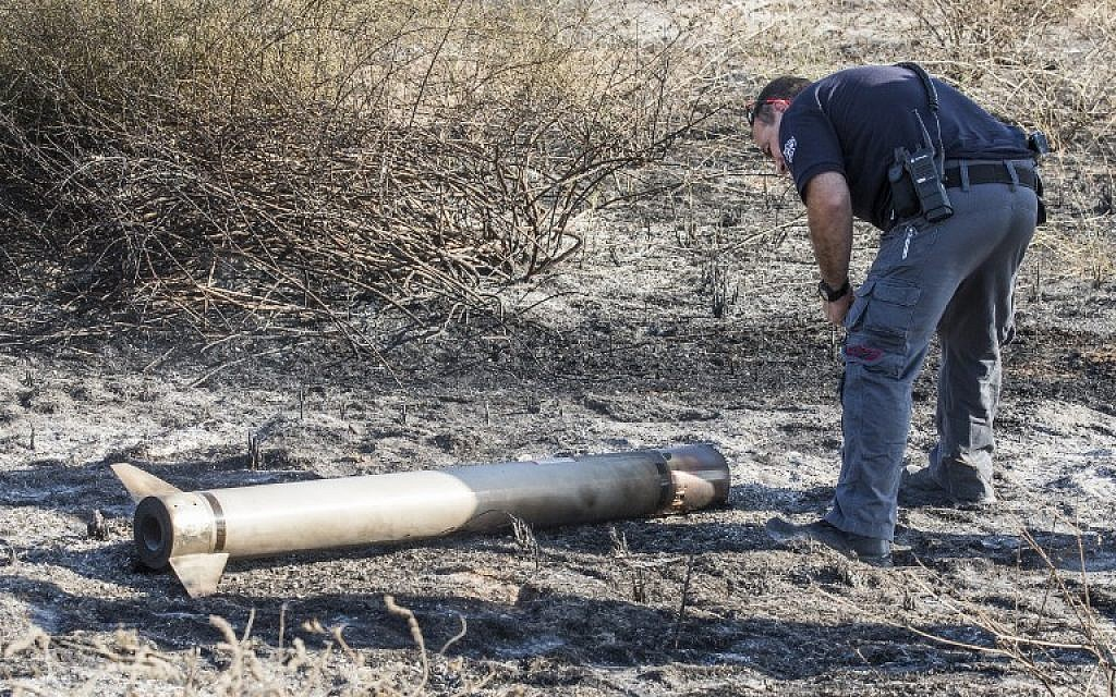An Israeli bomb disposal expert collects the remains of a missile launched by Israel's Iron Dome defence system and that had not exploded on August 26, 2014 along the Israeli Gaza border. (photo credit: AFP/Jack Guez)