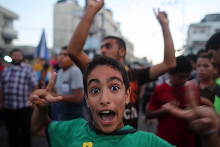 A Palestinian boy flashes the sign of victory as people gather in the streets of Rafah to celebrate after a deal was reached between Hamas and Israel over a long-term end to seven weeks of fighting, Tuesday, August 26, 2014 (photo credit: AFP/SAID KHATIB)