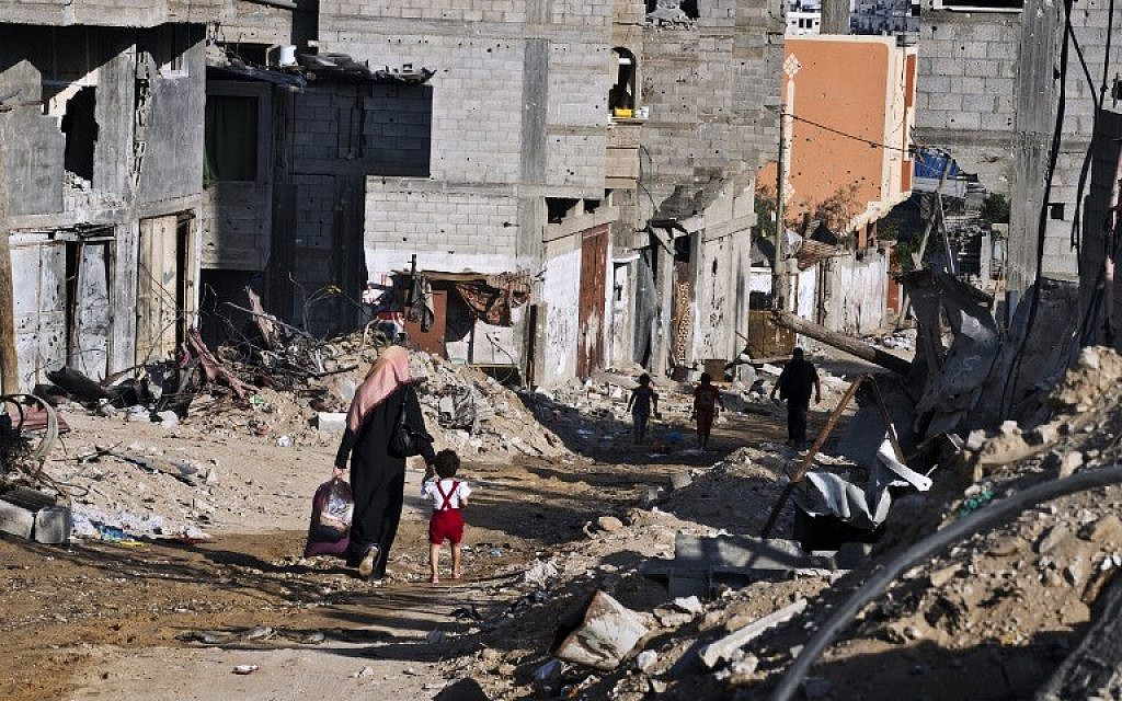 A Palestinian woman holds the hand of a child as they head home with some of their belongings on August 27, 2014, in Gaza City's Shejaiya neighborhood. (photo credit: AFP/Robert Schmidt)
