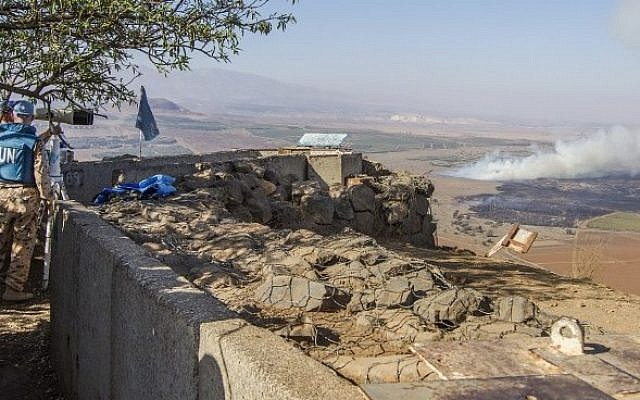UN peacekeepers use binoculars to watch smoke rising in the distance caused by fighting between forces loyal to Syrian President Bashar Assad and rebels over the control of the Quneitra border crossing, on August 27, 2014 (Photo credit: Jack Guez/AFP)