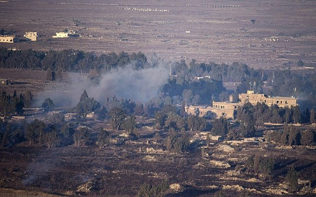 Smoke rises from the Syrian village of Quneitra, as seen from the Israeli Golan Heights, on August 27, 2014 (photo credit: AFP/JACK GUEZ)
