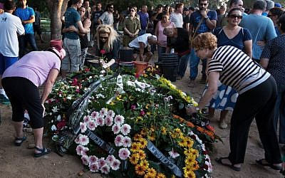 Israeli mourners lay flower wreaths on the grave of Shahar Melamed, 43, who was killed the previous day by Palestinian mortar fire in Kibbutz Nirim near Israel's border with the Gaza Strip, on August 27, 2014 (photo credit: AFP/MENAHEM KAHANA)