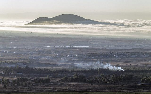 Smoke rise from the Syrian village of Quneitra, as seen from the Golan Heights, following fighting between forces loyal to Syrian President Bashar Assad and rebels over the control of the Quneitra border crossing, on August 28, 2014. (photo credit: AFP/JACK GUEZ)
