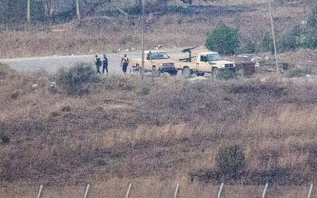 A picture taken from the Golan Heights shows armed men, reportedly rebel fighters, standing near vehicles in the Syrian side of the Golan, near the Quneitra border crossing, on August 28, 2014 (Photo credit: AFP/ JACK GUEZ)