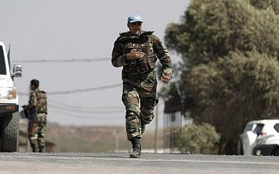 A UN peacekeeper runs past vehicles at the UN headquarters next to the Quneitra crossing, the only border crossing between Israel and Syria, in the Golan Heights on August 30, 2014 (Photo credit: Ahmad Gharabli/AFP)