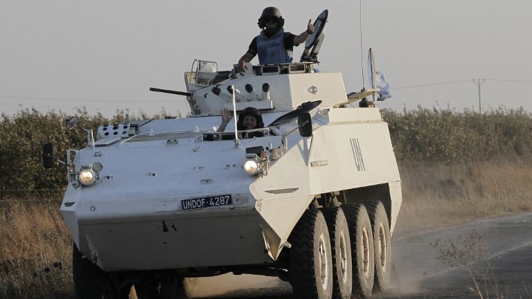 Members of the United Nations Disengagement Observer Force (UNDOF) wave as they drive their armored vehicle in the Golan Heights near the Quneitra crossing, on August 30, 2014 (AFP/Ahmad Gharabli)