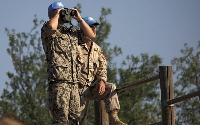 Members of United Nations Disengagement Observer Force (UNDOF) using binoculars to watch the Syrian side of the Golan Heights near the Quneitra border crossing, on August 31, 2014. (photo credit: AFP Photo/Jalaa Marey)