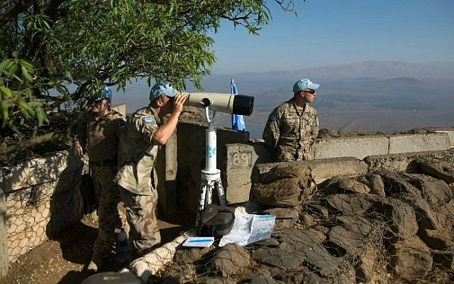 Members of UNDOF, the United Nations Disengagement Observer Force, use binoculars to watch Syrian positions from the Israeli Golan Heights on August 31, 2014. (photo credit: AFP/Menahem Kahana)