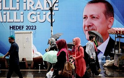 People walk past a campaign poster of Turkish Prime Minister Recep Tayyip Erdogan on Saturday, August 9, 2014, in Istanbul. (photo credit: Ozan Kose/AFP)