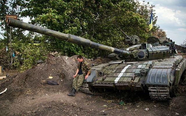 A Ukrainian serviceman sits on his tank on the frontline not far from the eastern Ukrainian city of Debaltseve, Donetsk region on August 25, 2014.  (photo credit: AFP/OLEKSANDR RATUSHNIAK)