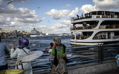 A Syrian woman (center) stands with her daughter near the Bosphorus on August 30, 2014, at Eminonu, in Istanbul. AFP Photo/Bulent Kilic)