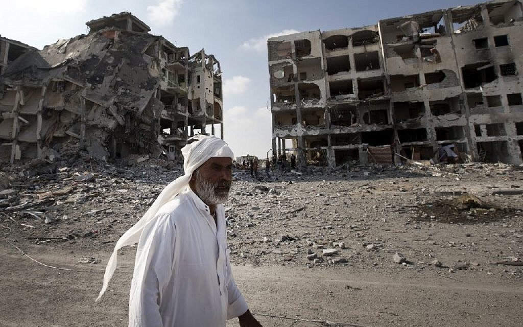A Palestinian man walks past destroyed buildings in the northern Gaza Strip on August 5, 2014. (photo credit:AFP/ MAHMUD HAMS)