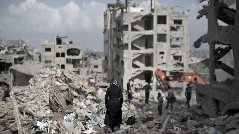 A Palestinian woman walks through the rubble of destroyed buildings in part of Gaza City's al-Tufah neighbourhood as the fragile ceasefire in the Gaza Strip enters a second day on Wednesday, August 6, 2014. (photo credit: Mahmud Hams/AFP)