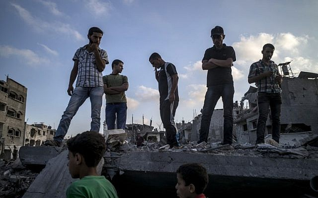 Palestinians stand on top of a destroyed building in the Gaza City neighborhood of Shejaiya, a Hamas stronghold from which hundreds of rockets have been launched at Israel, on August 6, 2014. (photo credit: AFP/MARCO LONGARI)