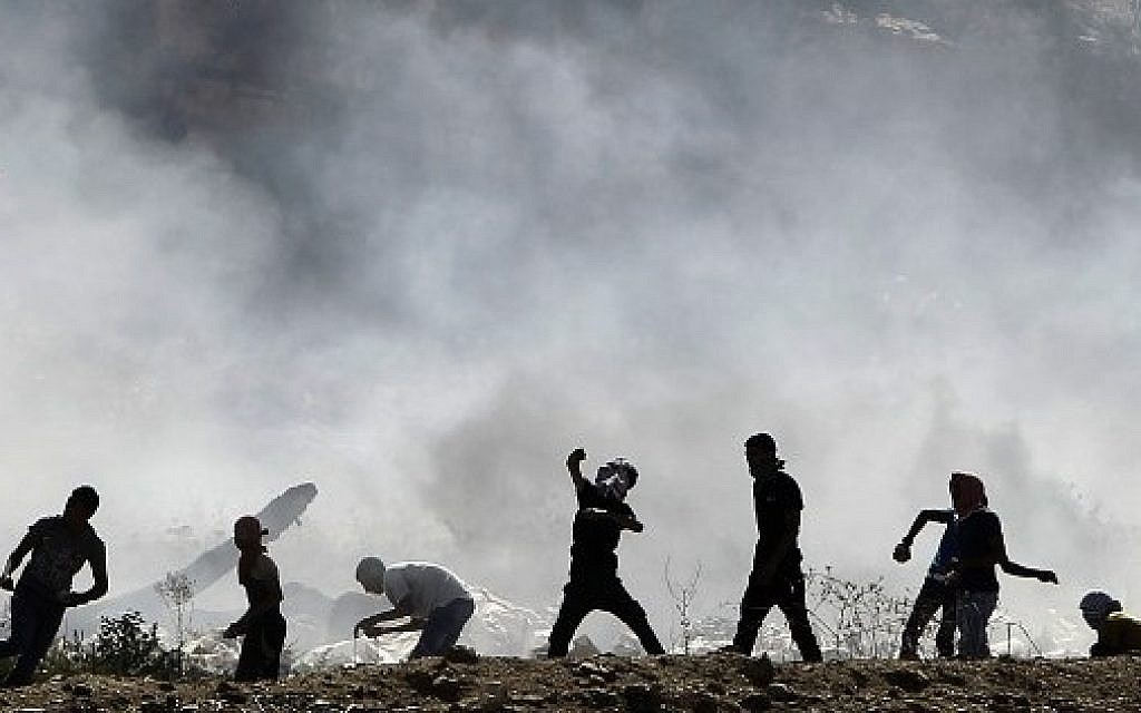 Palestinian protesters clash with Israeli security forces (unseen) following a demonstration in support of Gaza after Friday prayers at the Hawara checkpoint, east of the West Bank city of Nablus, on August 8, 2014 (Photo credit: Jaafar Ashtiyeh/AFP)