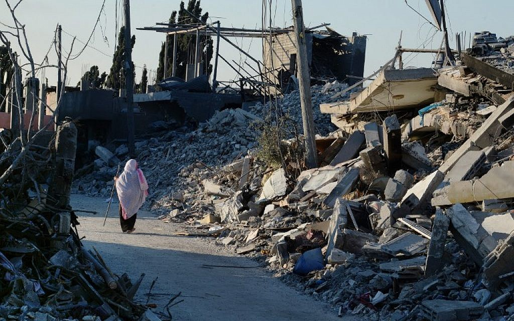 A Palestinian woman uses a piece of rebar she found amid the rubble, for support as she walks past destroyed homes in a street in Beit Hanoun, northern Gaza Strip, on August 12, 2014. (photo credit: AFP/ROBERTO SCHMIDT)