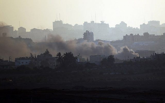 A picture taken from the Israeli side of the Israel-Gaza Border on August 21, 2014, shows smoke rising from buildings in the Gaza Strip after a rocket fired from Gaza landed short of its target (photo credit: AFP/DAVID BUIMOVITCH)
