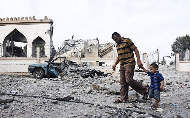 A Palestinian man walks with a child past the rubble of a mosque that was partially damaged by an Israeli airstrike on August 25, 2014 in Beit Lahia in the northern Gaza Strip. (photo credit: AFP/ROBERTO SCHMIDT)