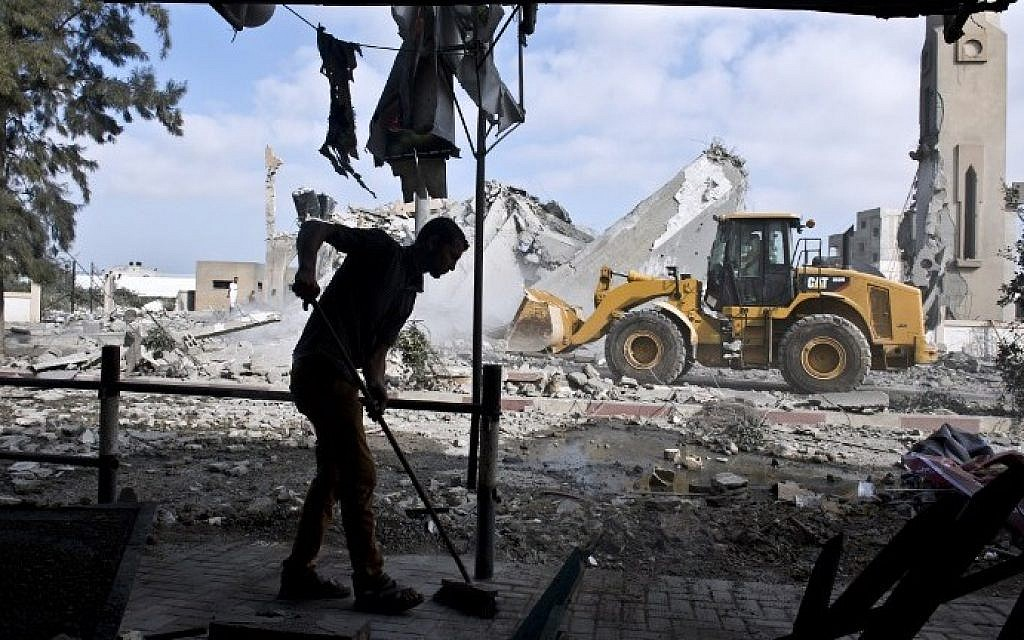 A Palestinian man sweeps the floor of his home that was damaged after a mosque across the street was hit by an Israeli airstrike on August 25, 2014 in Beit Lahia in the northern Gaza Strip. (photo credit: AFP Photo/Roberto Schmidt)