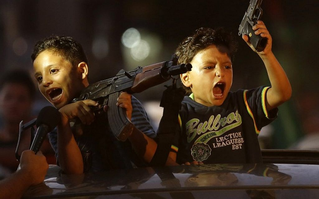 Children hold up guns (one with an empty magazine) from a car as Palestinians gather in the streets to celebrate after a deal had been reached between Hamas and Israel over a long-term end to seven weeks of fighting in the Gaza Strip on August 26, 2014 in Gaza City. (photo credit: AFP/Mohammed Abed)