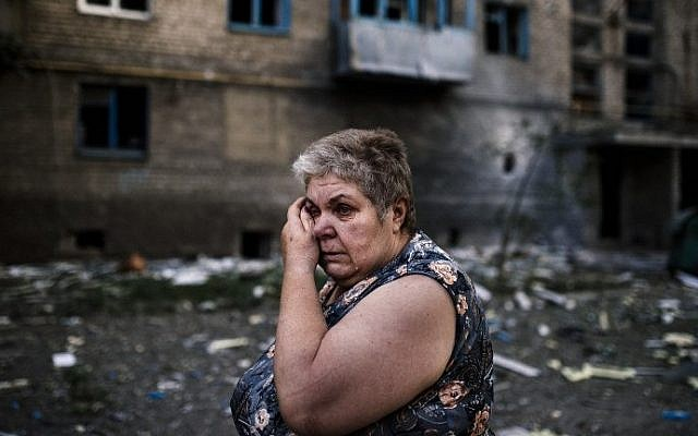 A woman reacts after shelling in the town of Yasynuvata near the rebel stronghold of Donetsk on August 12, 2014. (photo credit: Dimitar Dilkoff/AFP)