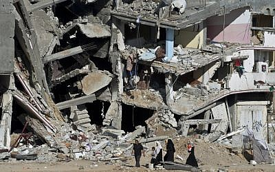 A Palestinian family walks on August 27, 2014, past the collapsed remains of a building in Shejaiya that was destroyed in fighting between Hamas and Israel. (photo credit: AFP/ROBERTO SCHMIDT)