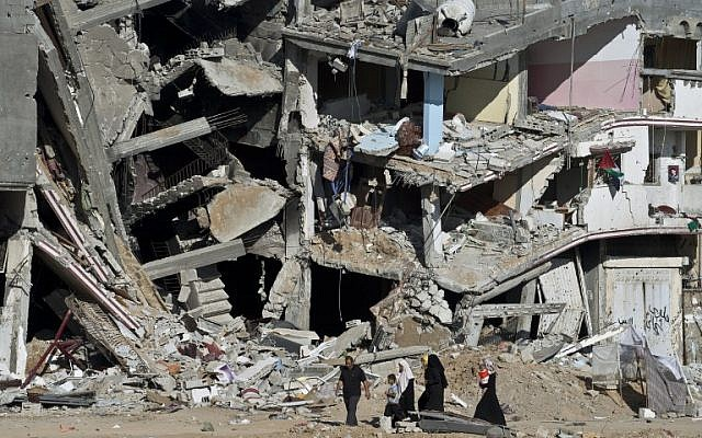 A Palestinian family walks on August 27, 2014, past the collapsed remains of a building in Shejaiya that was destroyed in fighting between Hamas and Israel. (AFP/ROBERTO SCHMIDT)