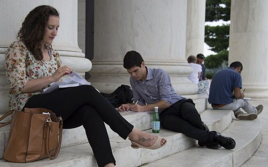 Noa Shusterman (L) and Daniel Nachum(C), Israeli students in the New Story Leadership (NSL) program, write a letter about their experiences outside the Thomas Jefferson Memorial in Washington, DC on August 1, 2014 (Photo credit: Jim Watson/AFP)