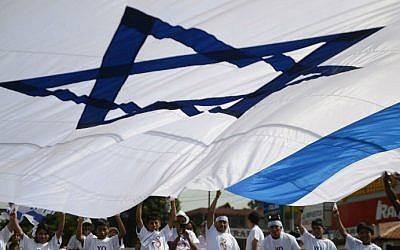 A pro-Israel group waves a huge flag during a demonstration in support of Israel during a military campaign in Gaza in the streets of Guatemala City on August 3, 2014. (photo credit: AFP Johan ORDONEZ)