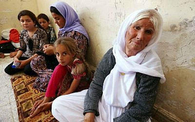 An Iraqi Yazidi family that fled the violence in the northern Iraqi town of Sinjar, sit at at a school where they are taking shelter in the Kurdish city of Dohuk in Iraq's autonomous Kurdistan region, on August 5, 2014. (photo credit: AFP/Safin Hamed)