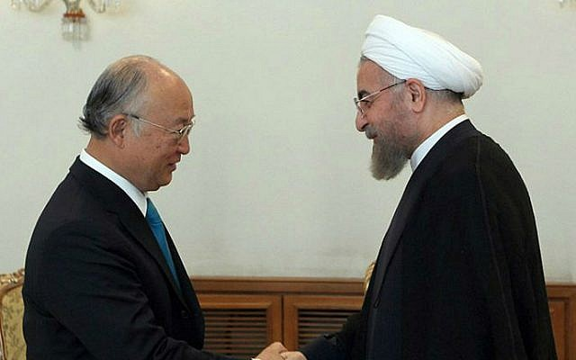 Iranian President Hassan Rouhani (right) shaking hands with Yukiya Amano (left), chief of the International Atomic Energy Agency (IAEA) during a meeting in Tehran on August 17, 2014. (photo credit: AFP/Iranian Presidency website/HO/Mohammad Berno)