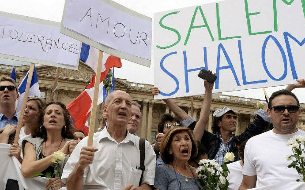 """Demonstrators hold French national flags and boards reading messages of peace in front of a Paris church as they take part in a demonstration gathering Jews and Muslims to advocate peace and fraternity in the context of the Israeli offensive in Gaza,  August 3, 2014. The signs read (from L) """"Tolerance"""", """"Love"""" and """"Salem Shalom"""". photo credit: AFP/PIERRE ANDRIEU)"""