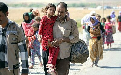 A displaced Iraqi man from the Yazidi community carries his daughter as they cross the Iraqi-Syrian border at the Fishkhabur crossing, in northern Iraq, on August 11, 2014. (photo credit: AFP/AHMAD AL-RUBAYE)