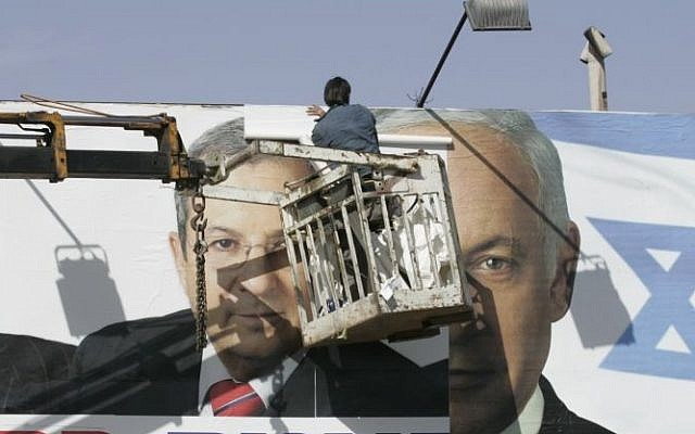 Workers replacing a Labor Party campaign poster with a Likud one in Jerusalem, Jan. 30, 2009.  (photo credit: Yossi Zamir /Flash90)