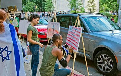 In New York's Village, passersby participate in the Artists 4 Israel 'Art Vigil' as a pro-Israel rally takes place in the next block. (courtesy)