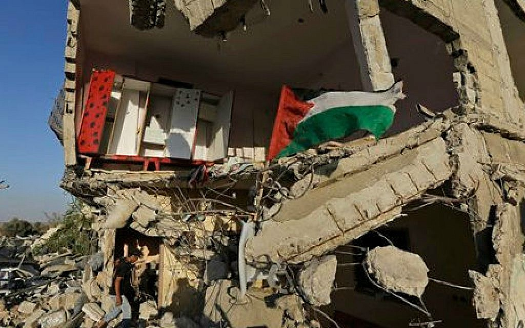 A Palestinian walks into a house, destroyed by an Israeli strike in the Gaza City neighborhood of Shejaiyah, a Hamas stronghold from which hundreds of rockets were fired at Israel, as the national flag flies on the rubble, Thursday, Aug. 7, 2014 (photo credit: AP/Lefteris Pitarakis)