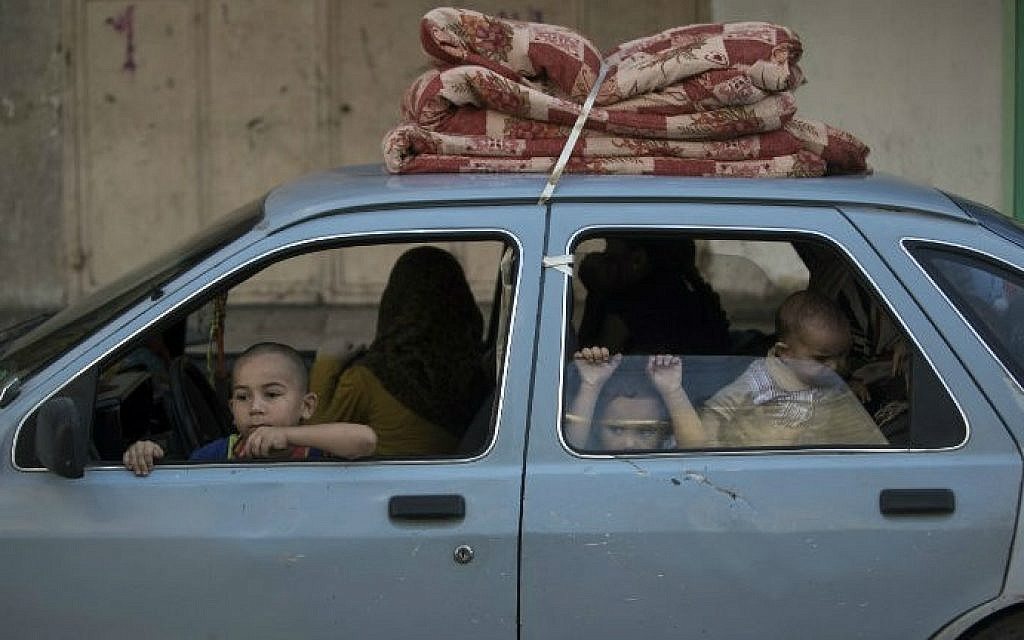 Palestinian families leave their homes in Gaza City's Shejaiya neighborhood in fear of Israeli attacks, after Palestinian factions in Gaza refused to extend the 72-hour ceasefire with Israel and opened fire on Israel, on August 8, 2014 (photo credit: AFP/ Mahmud Hams)