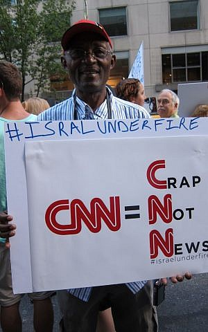 Stephen Tebid, a retired journalist, holds a sign saying 'CNN=Crap Not News' at protest in New York on August 8, 2014. (Cathryn J. Prince/The Times of Israel)