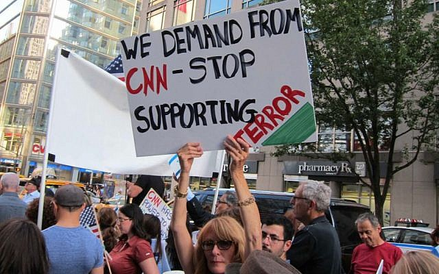 Woman at protest in front of CNN headquarters August 8, 2014 holds a sign saying, 'We demand from CNN = stop supporting terror' (Cathryn J. Prince/The Times of Israel)