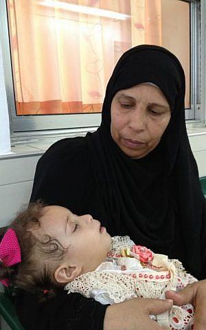 Haniyah Shaer holds her sleeping granddaughter Hala Aradha following her checkup, August 12, 2014 photo credit: Elhanan Miller/Times of Israel)