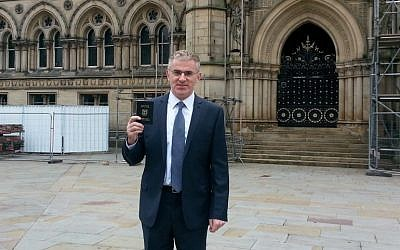 Ambassador Daniel Taub holds up his Israeli passport in Bradford, UK, which was declared an 'Israel-free zone' by Respect MP George Galloway, on August 18, 2014. (Photo credit: Evelyn Coster)