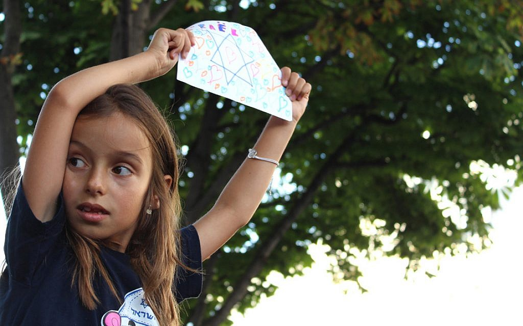 A young girl wears a shirt with Hebrew writing and holds a hand-drawn Star of David at the pro-Israel rally on July 31, 2014. (Glenn Cloarec/The Times of Israel)