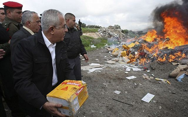 Former Palestinian prime minister Salam Fayyad throws a package into a fire set to burn products from Jewish settlements, in the West Bank of Salfit, January 5, 2010 (photo credit: AP/Nasser Ishtayeh)